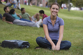 Woman sitting on grass on campus