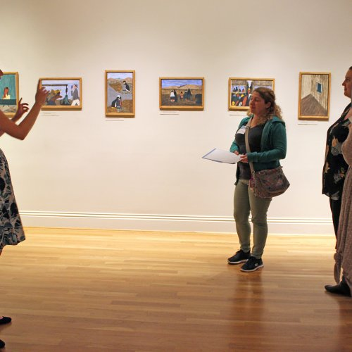 Woman standing in front of students in a museum