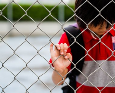 Boy stands behind fence