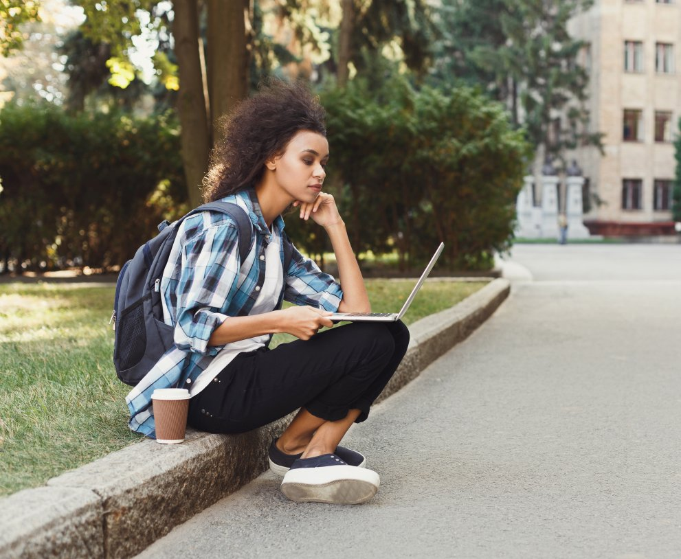 Woman sits on curb at college campus
