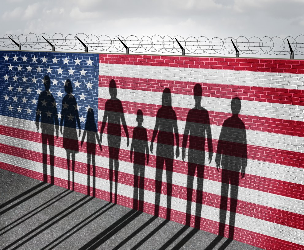American flag wall with barbed wire and human silhouettes