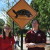 two student ambassadors in front of turtle crossing sign