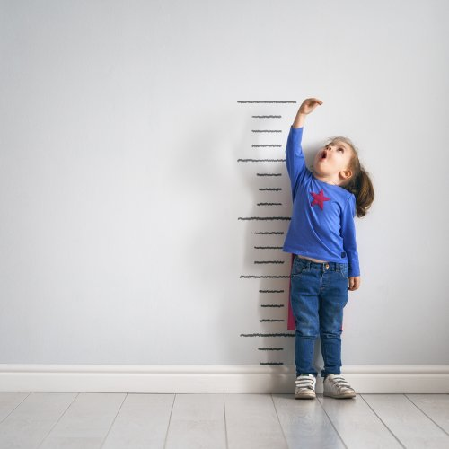 girl measuring her height against wall stock photo