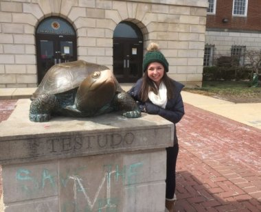 Girl dressed in a jacket and hat posing next to Testudo and smiling