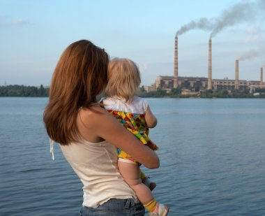 Child looking at smoke stacks with mom