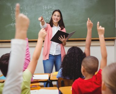 teacher in classroom with students hands raised